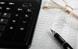 Calculator, pen, glasses and financial documentation